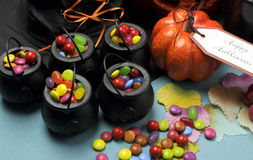 Halloween Trick or Treat party table. Close up. Halloween Trick or Treat party table with witch hat and cauldrons full of candy, ornage pumpkin, jack o lantern Stock Image