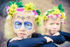 Halloween twin girls with sugar skull makeup Stock Image