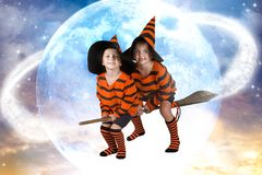 Halloween.Two of the boy wizard fly on broomstick across the sky.Beautiful children in Halloween costumes. stock images