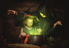 Halloween. two witches old and young preparing  potion in cauldr Stock Image