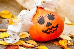 Halloween uma abóbora alegre de Dia das Bruxas entre as folhas Foto de Stock