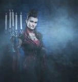 Halloween: un vampiro de la señora joven que lleva a cabo velas Fotos de archivo libres de regalías