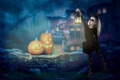 Halloween, vakantie, maskeradeconcept - het portret van jongelui weinig mooi meisje met schedelmake-up op pompoenenachtergrond Ha royalty-vrije stock foto