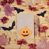 Halloween-vakantieachtergrond, leeg document voor tekst, pompoen, pen, esdoornbladeren, bessen, en knuppel Mening van hierboven Stock Fotografie