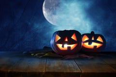 Halloween-vakantieconcept Lege rustieke lijst voor Pompoenen over houten lijst bij nacht enge, achtervolgde en nevelige bosrea stock foto