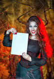 Halloween vampire holding sheet of paper Stock Images