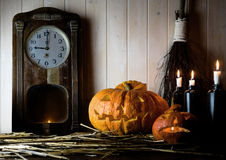 Halloween. Vintage interior in western style. candles, antique clock, broom and glowing pumpkin Stock Photos