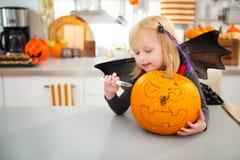 Halloween vistió a la muchacha que creaba la Jack-O-linterna grande de la calabaza Imágenes de archivo libres de regalías