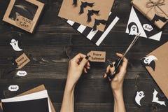 Halloween-voorbereiding Handen Halloween-kaarten maken en decoratie die ambachtdocument gebruiken Royalty-vrije Stock Afbeeldingen