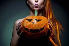 Halloween, vrouw in ondergoed met pompoen in zijn handen Portret op donkergroene achtergrond stock foto