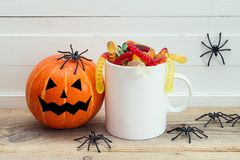 Halloween white coffee mug with candy worms, pumpkin and spiders Royalty Free Stock Image