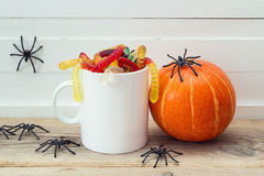 Halloween white coffee mug with candy worms, pumpkin and spiders Stock Image