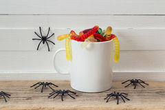 Halloween white coffee mug with candy worms and spiders. Royalty Free Stock Photo