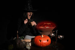 Halloween witch. Stirring in red poison soup in her cauldron Royalty Free Stock Photo