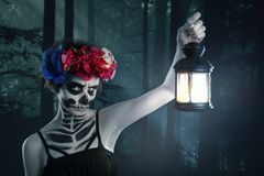 Halloween witch. Beautiful woman wearing santa muerte mask casting spell stock photography