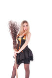 Halloween witch in black dress with broom. Royalty Free Stock Photography