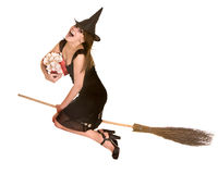 Halloween witch in black dress and hat on broom. Royalty Free Stock Photos