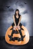 Halloween witch. Halloween black sexy witch sitting on jack o lantern on grunge background Royalty Free Stock Photo