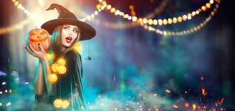 Halloween. Witch with a carved pumpkin and magic lights. In a dark forest royalty free stock image