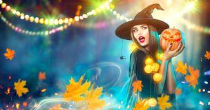 Halloween witch with a carved pumpkin and magic lights Stock Images