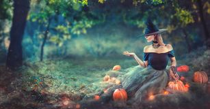Halloween Witch with a carved pumpkin and magic lights in a dark forest at night. Beautiful young woman in witches costume