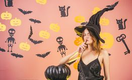 Halloween Witch with a carved Pumpkin and magic lights in a dark forest. Halloween party. Models Posing on royalty free stock photography