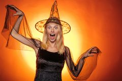 Halloween Witch with a carved Pumpkin and magic lights in a dark room. Halloween party and holiday concept. Halloween. Witch with pumpkin. Funny face. Crazy stock photo