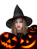 Halloween witch with a carved pumpkin stock images