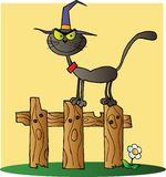 Halloween witch cat on a fence over yellow Stock Photo