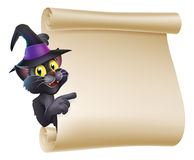 Halloween Witch Cat Scroll. Cartoon Halloween black cat wearing witch hat  peeping round a scroll sign and pointing at what is written on it Royalty Free Stock Photos