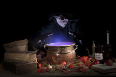Halloween witch with cauldron. Halloween making a potion in a copper cauldron Royalty Free Stock Image