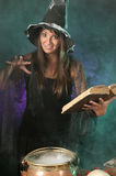 Halloween witch cauldron. Halloween witch on smoky green and purple background Royalty Free Stock Images