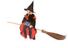 Halloween witch child girl in hat fly on broom. Child girl in costume Halloween witch in black dress and hat fly on broom.Isolated royalty free stock photography