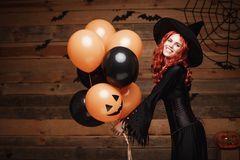 Halloween Witch Concept - Beautiful caucasian woman in witch costumes celebrating Halloween posing with posing with orange and bla. Ck balloon over bats and royalty free stock photos