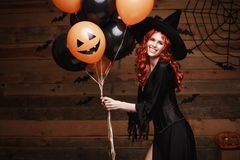 Halloween Witch Concept - Beautiful caucasian woman in witch costumes celebrating Halloween posing with posing with orange and bla. Ck balloon over bats and royalty free stock photography