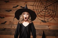 Halloween Witch concept - closeup shot of little caucasian witch child shocking face posing with bat and spider web on wooden stud Royalty Free Stock Photography