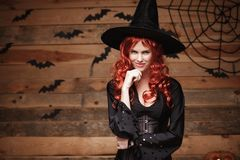 Halloween witch concept - Happy Halloween red hair Witch holding hand on her chin posing over old wooden studio background. Royalty Free Stock Photo