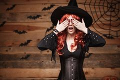 Halloween witch concept - Happy Halloween red hair Witch holding hands closing eyes posing over old wooden studio. Background stock image