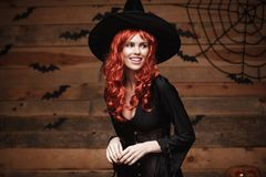 Halloween witch concept - Happy Halloween red hair Witch holding posing over old wooden studio background. Royalty Free Stock Photo