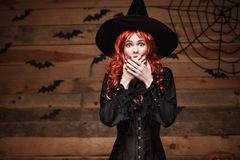 Halloween witch concept - Happy Halloween red hair Witch holding posing with shocked face over old wooden studio background. Stock Images