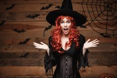 Halloween witch concept - Happy Halloween red hair Witch holding posing with shocked face over old wooden studio background. Royalty Free Stock Photography