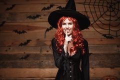 Halloween witch concept - Happy Halloween red hair Witch doing silence gesture with finger on her lips over old wooden studio back Stock Photos