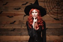 Halloween witch concept - Happy Halloween red hair Witch doing silence gesture with finger on her lips over old wooden studio back Stock Images