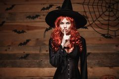 Halloween witch concept - Happy Halloween red hair Witch doing silence gesture with finger on her lips over old wooden studio back Royalty Free Stock Images