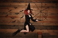 Halloween witch concept - Happy Halloween red hair Witch holding magic broomstick flying gesture over old wooden studio background Royalty Free Stock Photo