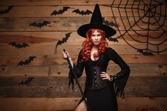 Halloween witch concept - Happy Halloween red hair Witch holding posing with magic broomstick over old wooden studio background. stock photography