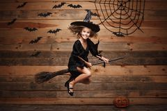 Halloween Witch concept - little caucasian witch child flying on magic broomstick over bat and spider web background. Stock Photo