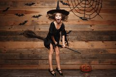 Halloween Witch concept - little caucasian witch child flying on magic broomstick over bat and spider web background. Royalty Free Stock Image