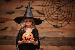 Halloween Witch concept - little caucasian witch child disappointing with no candy in halloween candy pumpkin jar. over bat and sp. Ider web background stock images