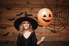 Halloween Witch concept - little caucasian witch child enjoy with halloween balloon. over bat and spider web background. Royalty Free Stock Images